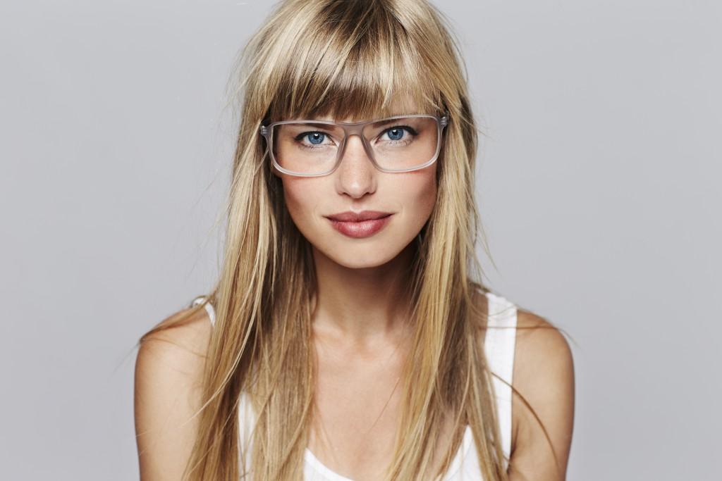 Blonde junge Frau mit einer hellen Brille passend zum blonden Haar